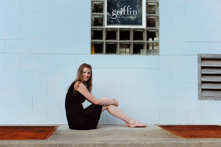 High school senior girl sitting on concrete slab in front of blue wall.
