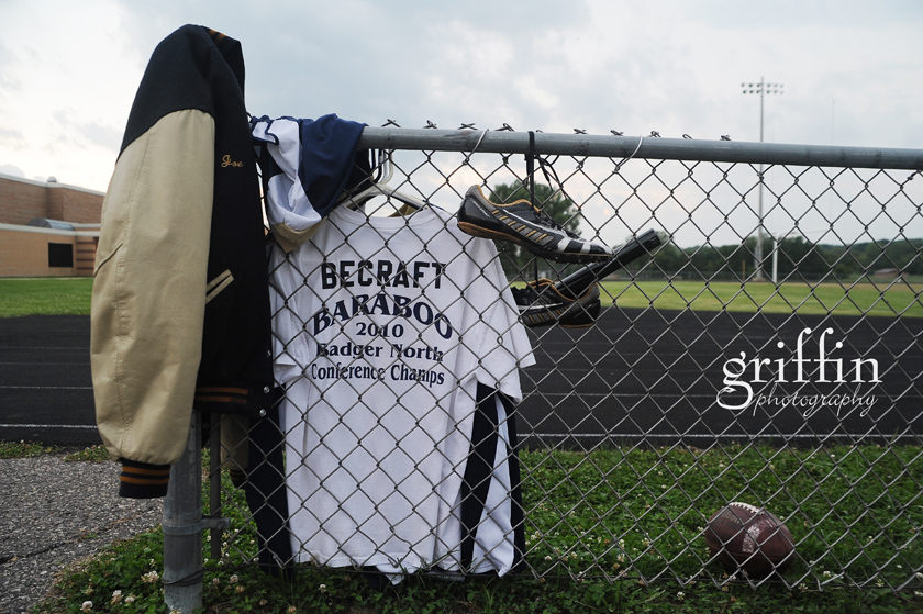 senior boy's gear hanging on fence.