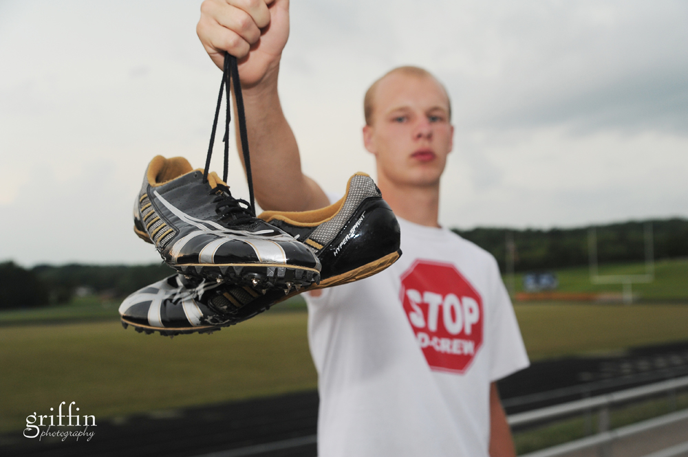 senior boy showing off his running shoes.