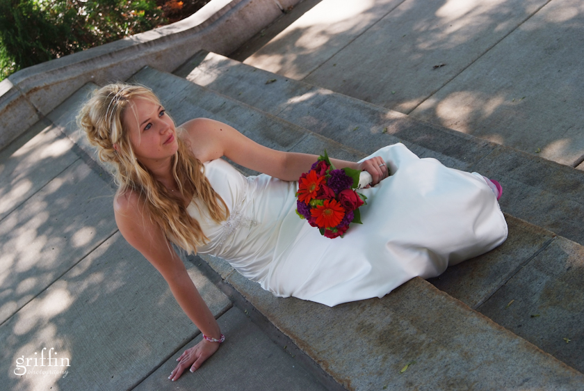 the gorgeous bride seated on cement steps awaiting her formals.