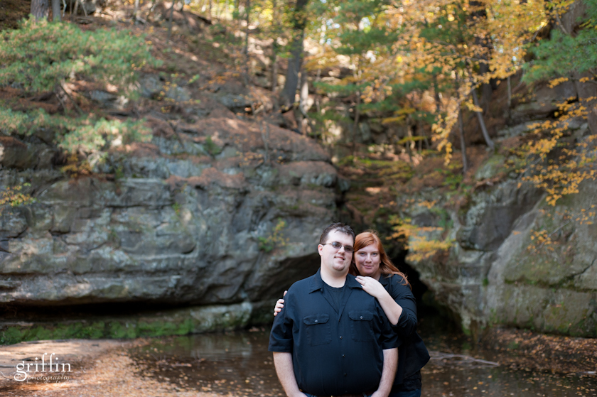 Waterfall behind engaged couple with fall colors in Southwestern Wisconsin.