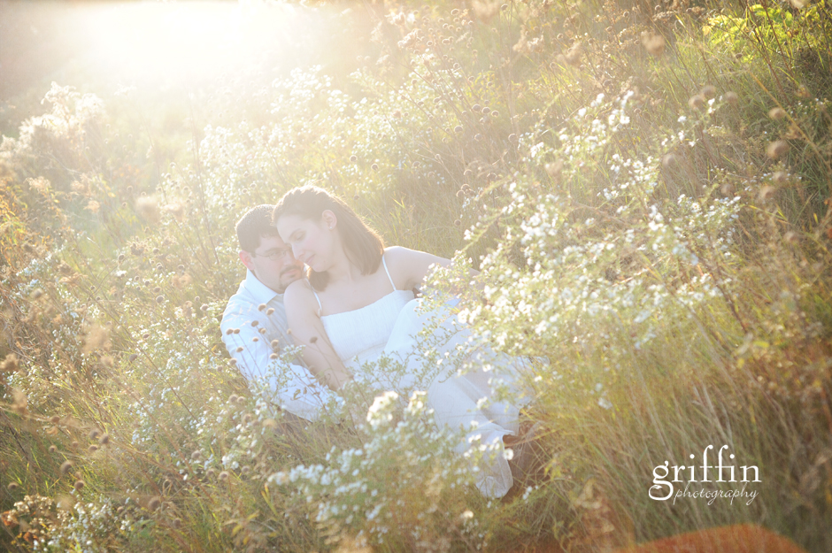 Bride and groom seated in flower field at sunset.