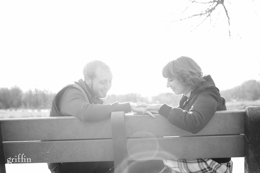 Engaged couple sitting on bench holding hands.