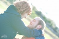 Girl holding on to her man with sun flare surrounding them.