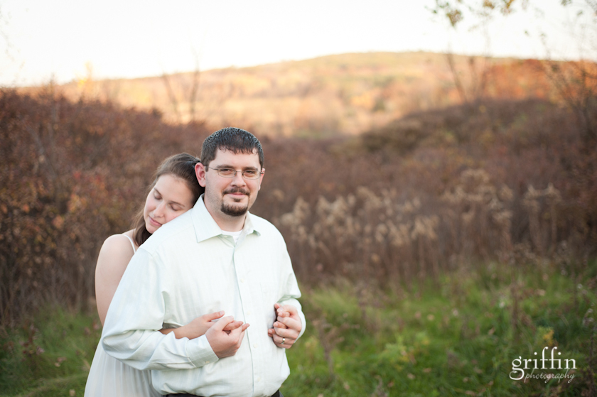 Bride hugging husband with Baraboo bluffs behind them in the background.