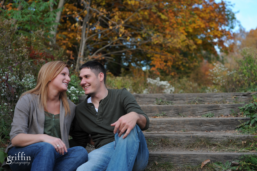 Engaged couple sitting on wooden steps looking at each other.