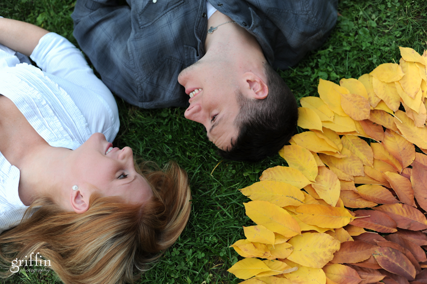 Man and woman laying on grass next to leaf art.