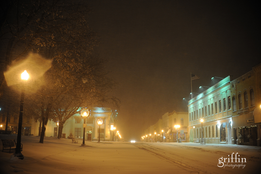 Downtown Baraboo Wisconsin covered in snow, twinkling lights down the street.