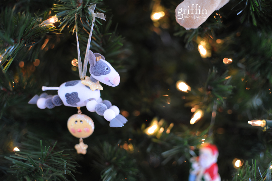 Cow jumping over the moon Hallmark ornament hanging on tree.