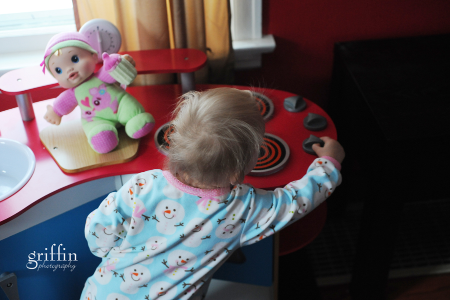 Toddler playing with the knobs on her Melissa and Doug kitchen playset.