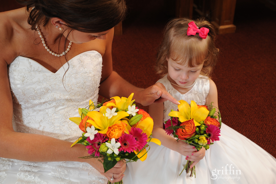 The bride and flowergirl comparing bouquets.