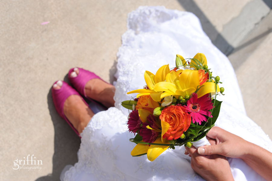The bride's bouquet and magenta shoes.