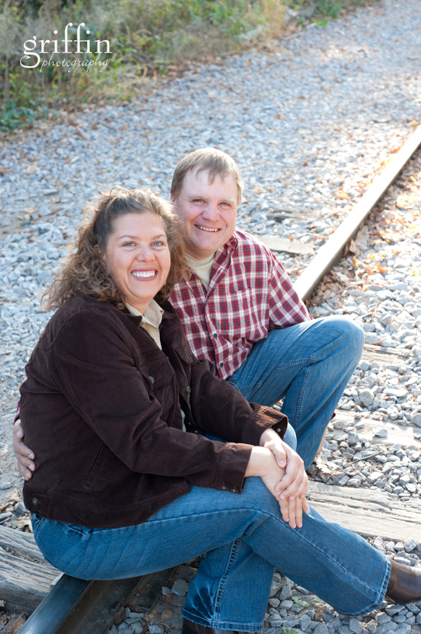 Husband and wife sitting on the train tracks.