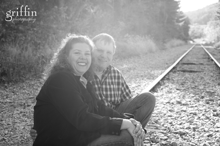 black and white of couple sitting on the train tracks.