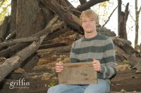 Senior sitting on tree fort with homemade Fort Herman sign.
