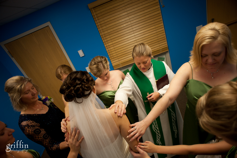 Officiant and bridesmaids praying with hands on bride.