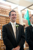 The smiling groom awaiting his bride to be as she walks down the aisle.