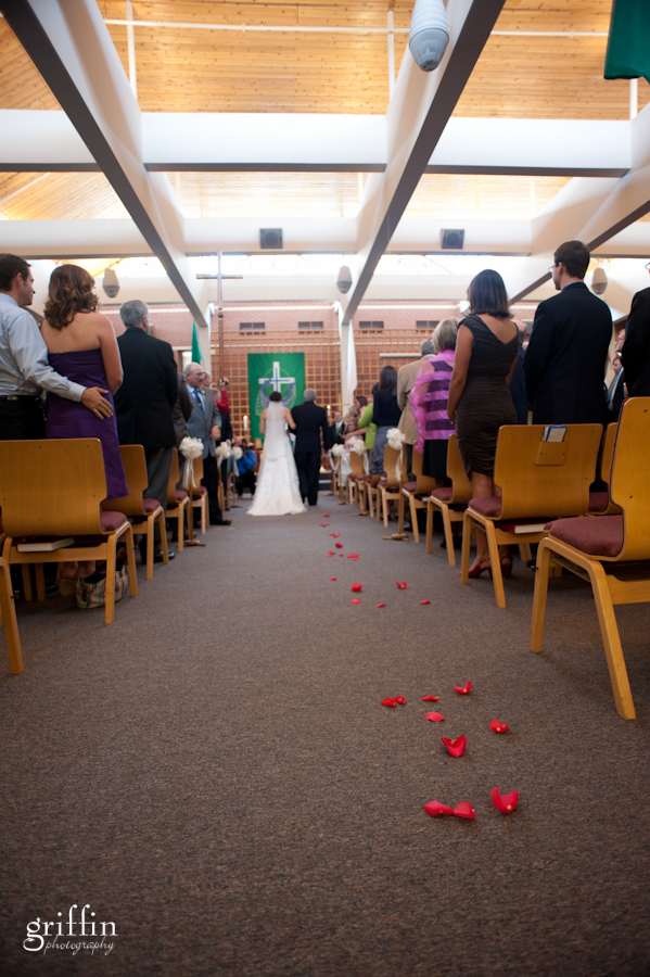 Rose petals strewn on the floor of the aisle.