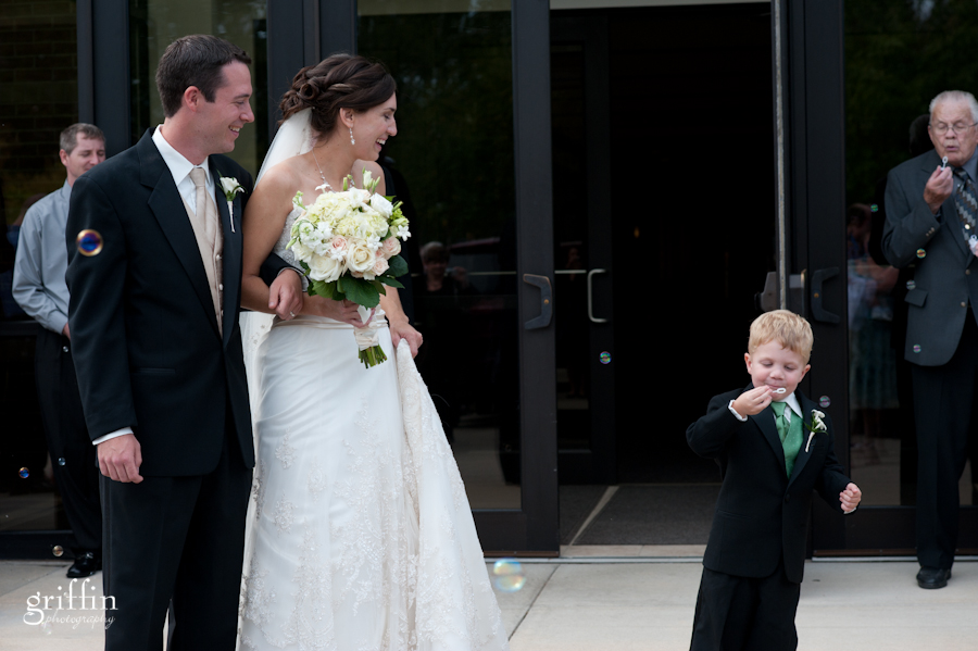 Ringbearer blowing bubbles for the bride and groom.