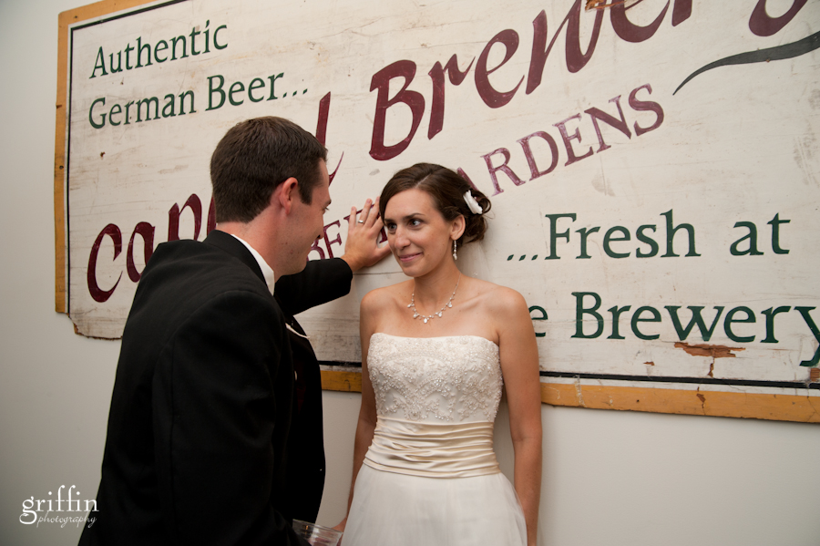 Bride and groom in front of Capital Brewery sign in Madison Wisconsin as captured by Griffin Photography.