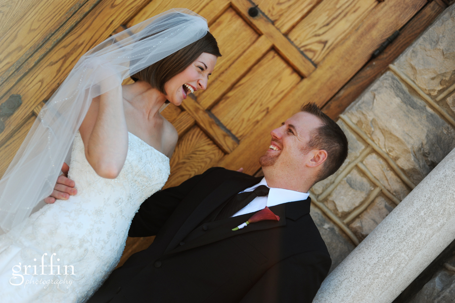 Bride and groom laughing in front of wooden church door at St. Joe's in Baraboo Wisconsin.