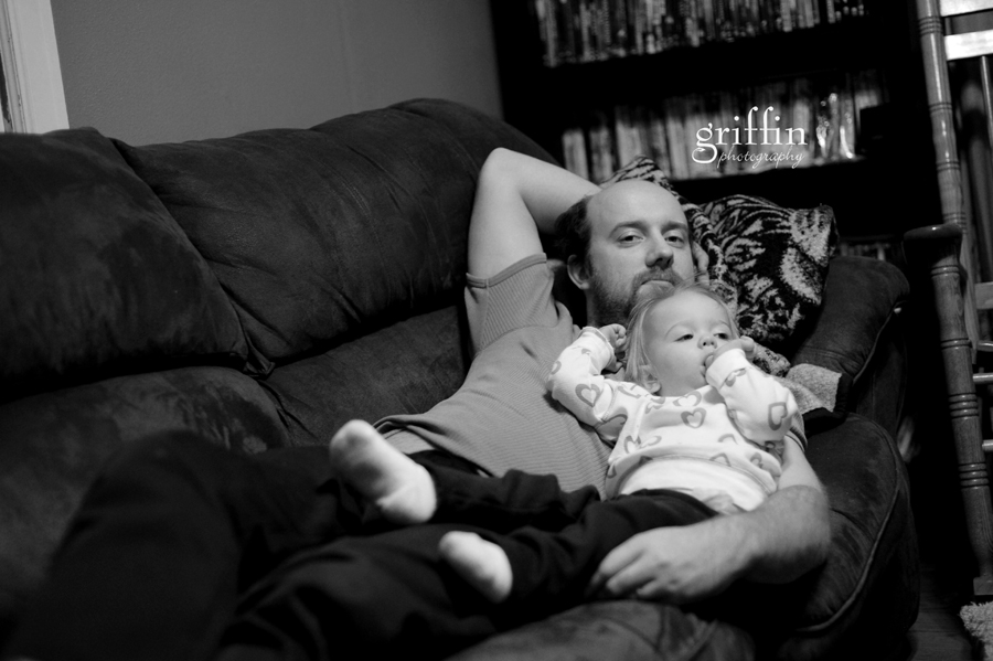 Father and daughter lounging on the couch.