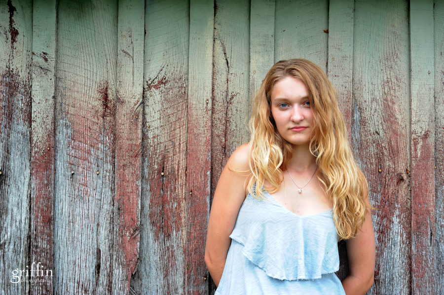 senior portrait of girl in front of distressed wood wall.
