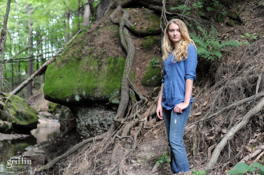 Female senior portrait with gnarled roots as background.
