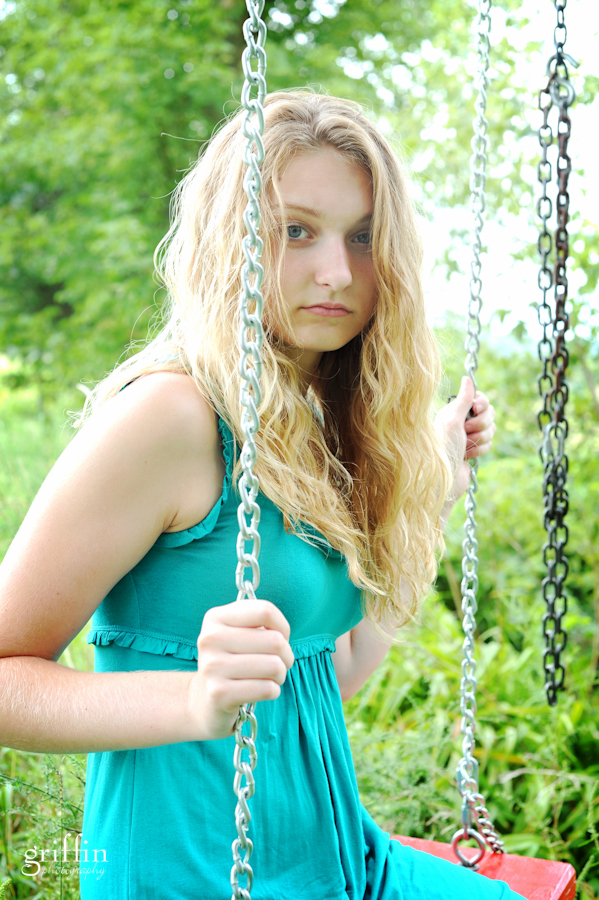 Female senior portrait on red swing.