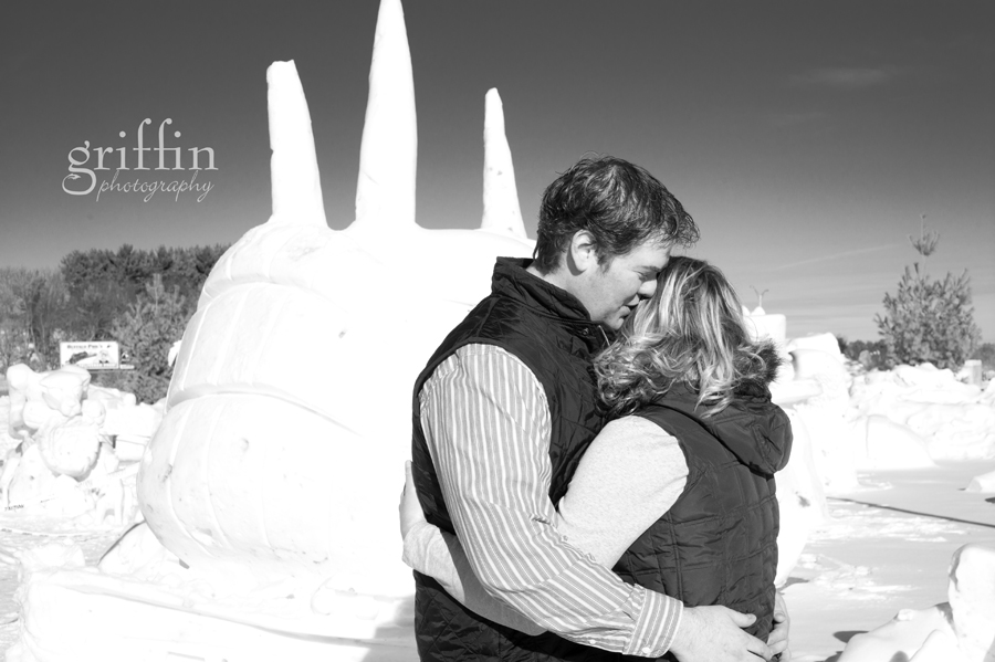 pirate ship snow sculpture behind engaged couple hugging.