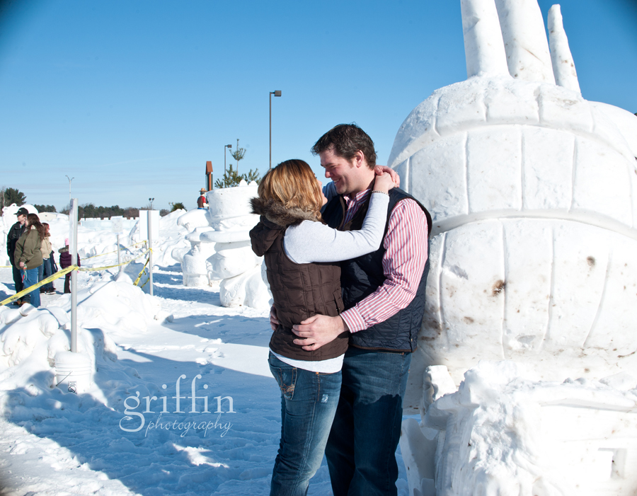 engaged couple in wisconsin dells next to snow sculpture.