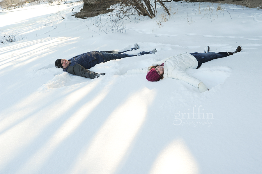Engaged couple making snow angels in the snow along the Wisconsin River.