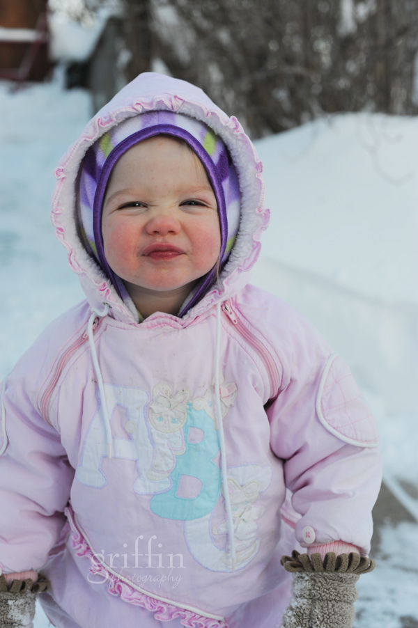 Toddler smiling at the camera while surrounded by snow in Wisconsin.