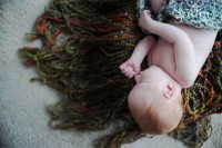 Baraboo newborn photography with fringe blanket in basket.