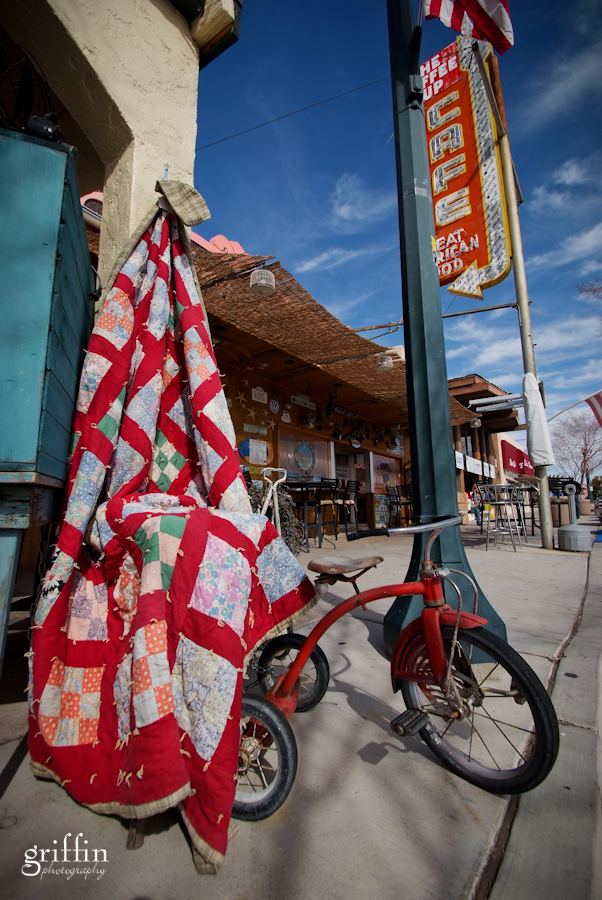 Tricycle and quilt on display in Boulder city on the sidewalk.