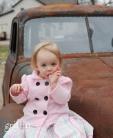 Child sitting on the hood of a rusted Chevy truck.