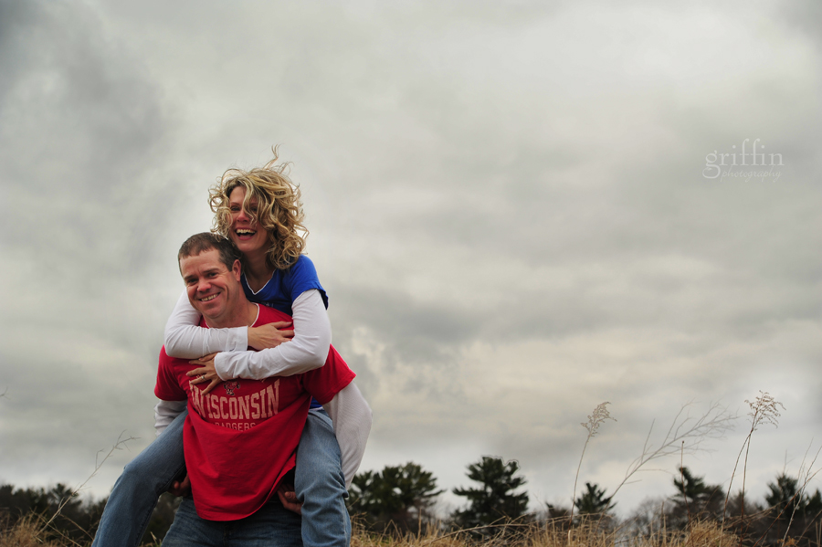 Storm clouds behind the couple as they give a piggy back ride.