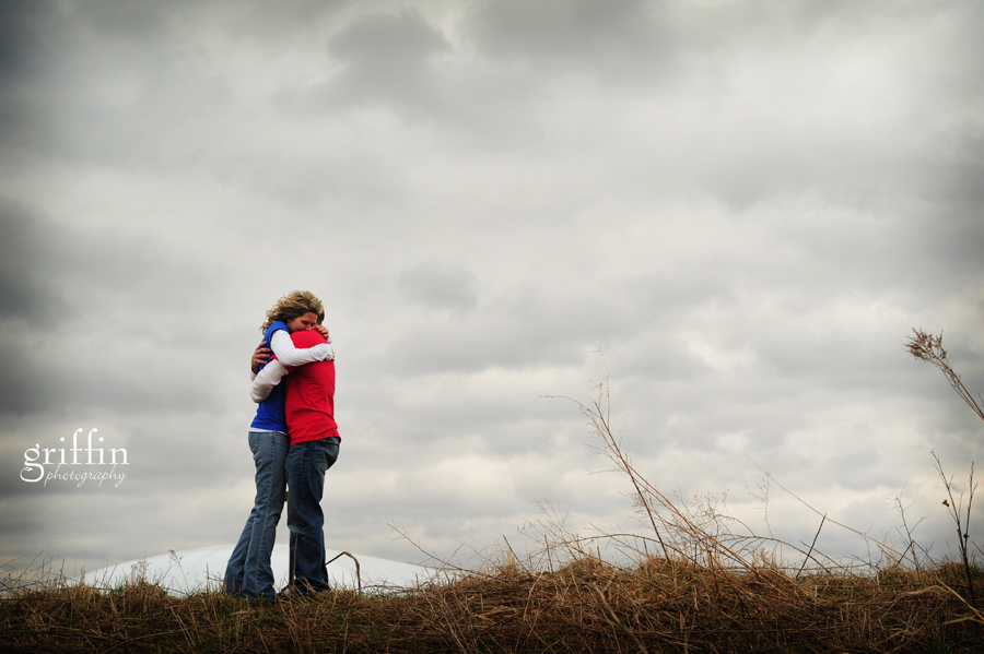 Engaged couple hugging with storm clouds behind them.