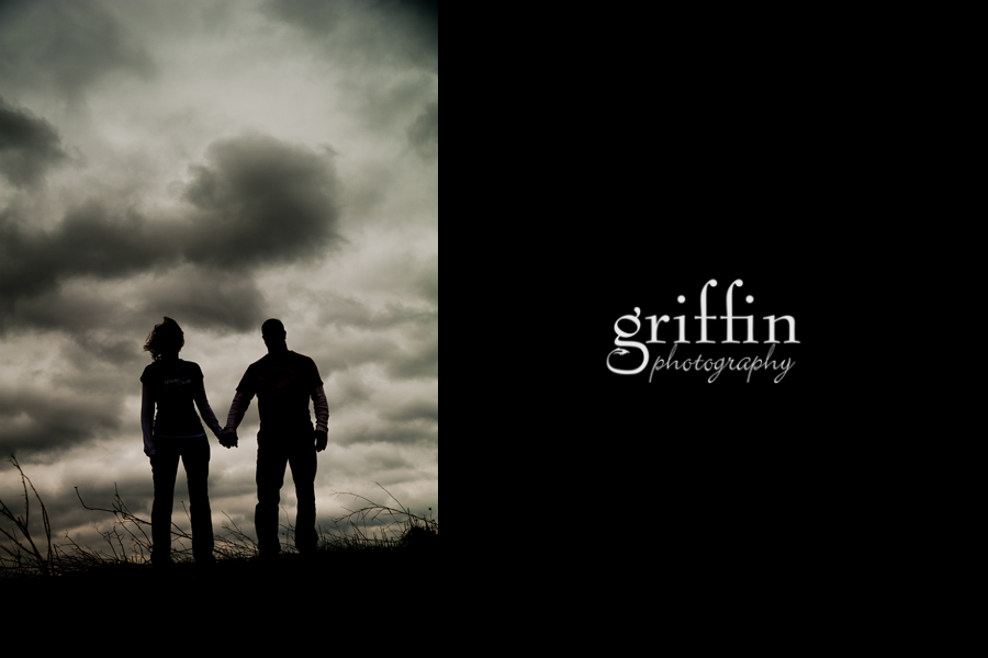 Silhouette of engaged couple with storm clouds.