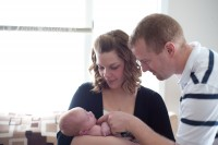 New parents marveling at their little one, Baraboo newborn photographer.