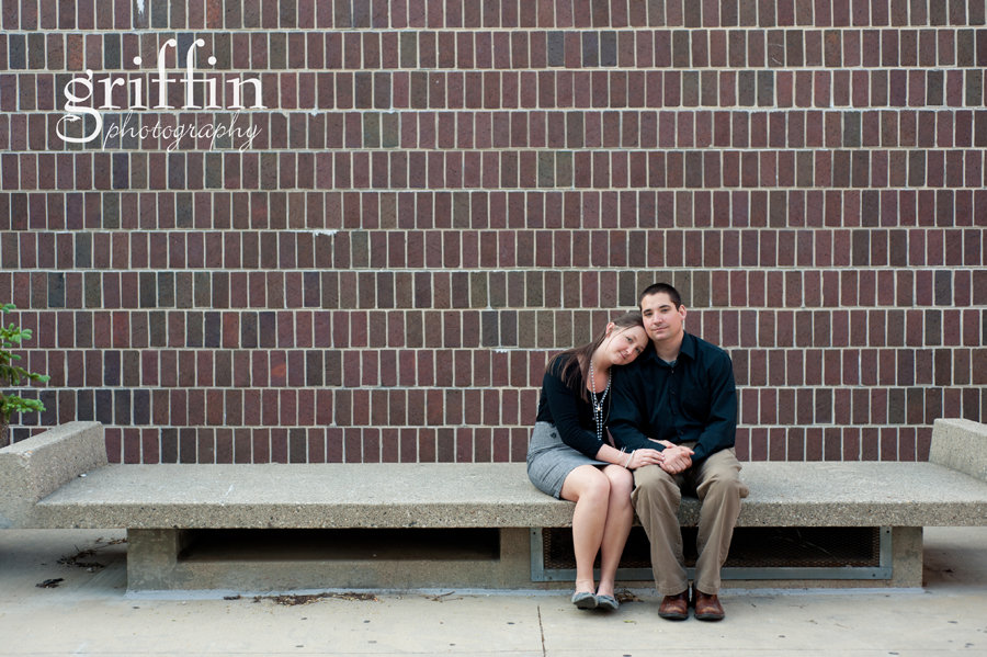 Engaged couple in front of brick wall sitting on concrete bench.