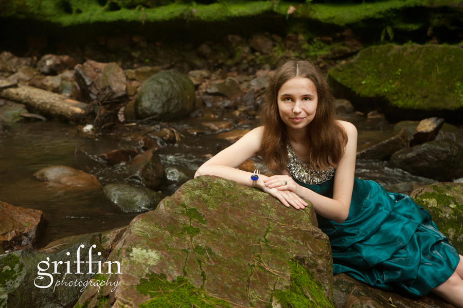 Senior photography girl in prom dress with moss covered rock.