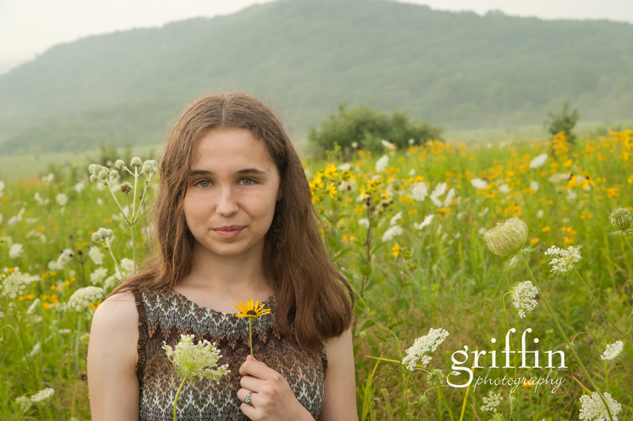 Girl holding black eyed susan for school photo in the misty rain.