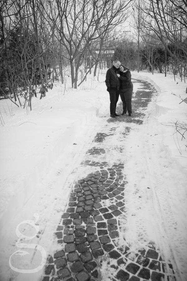 Black and white of engaged couple standing down a cobblestone path.