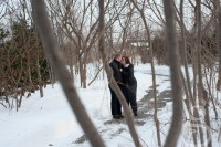 Couple kissing through the trees.