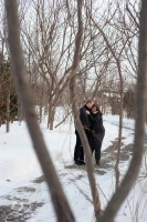 Engaged couple laughing through the trees.
