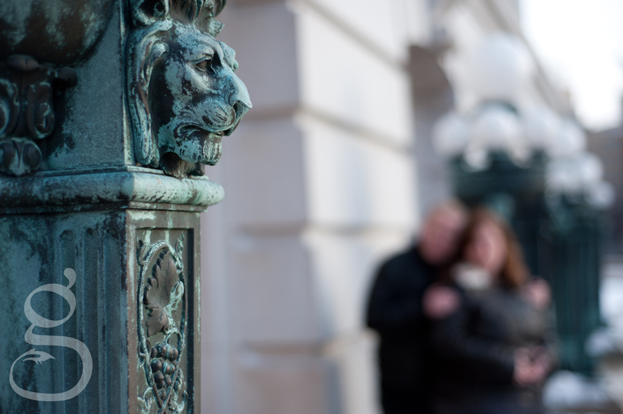 Bronze lion pillar with couple in bokeh background.