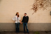 Couple in love holding hands against a cream and grey wall.