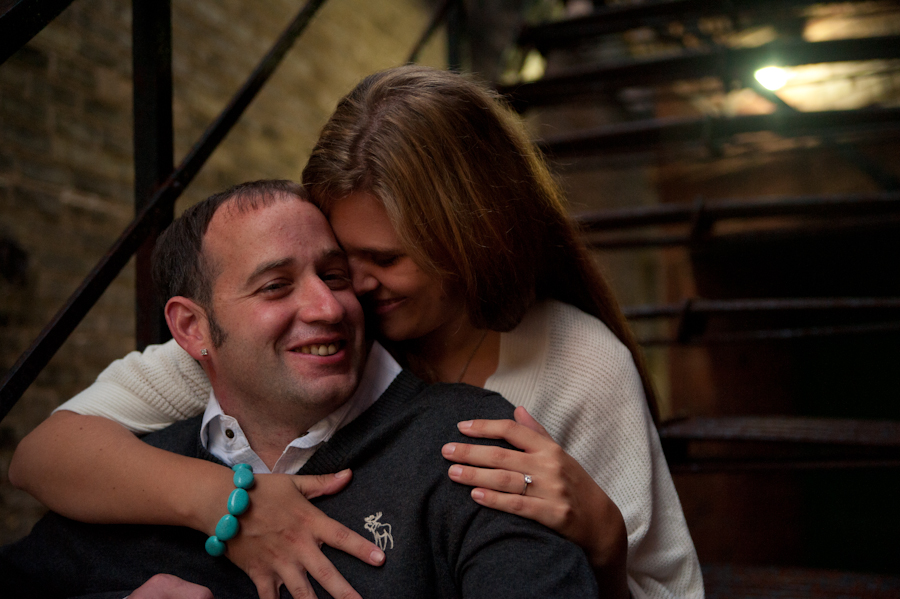 Engaged couple laughing on wrought iron staircase.