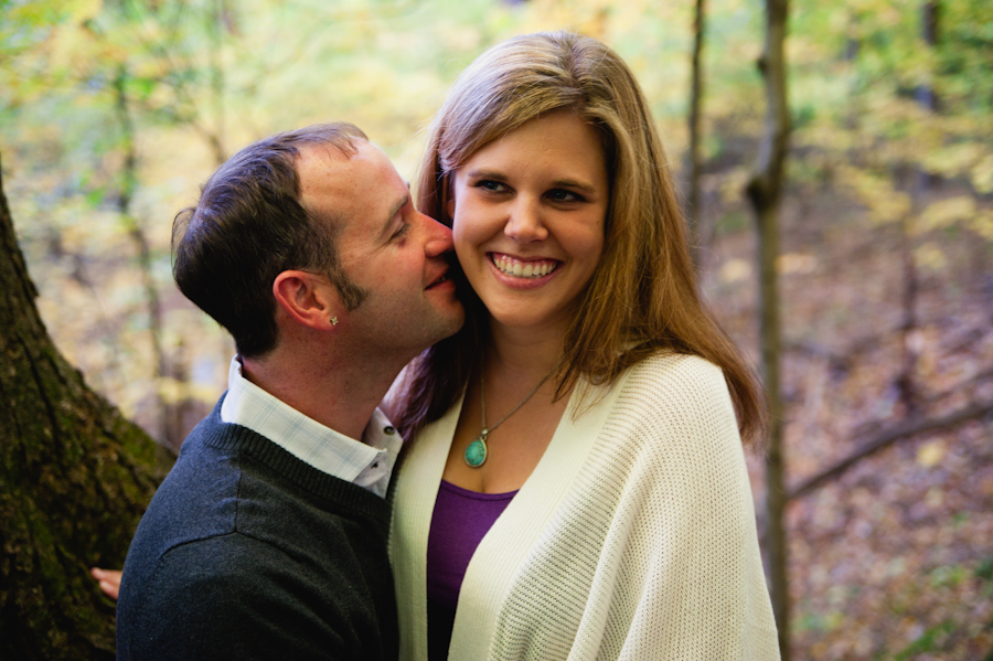 Engaged couple nuzzling at the engagement session under cover of fall leaves.